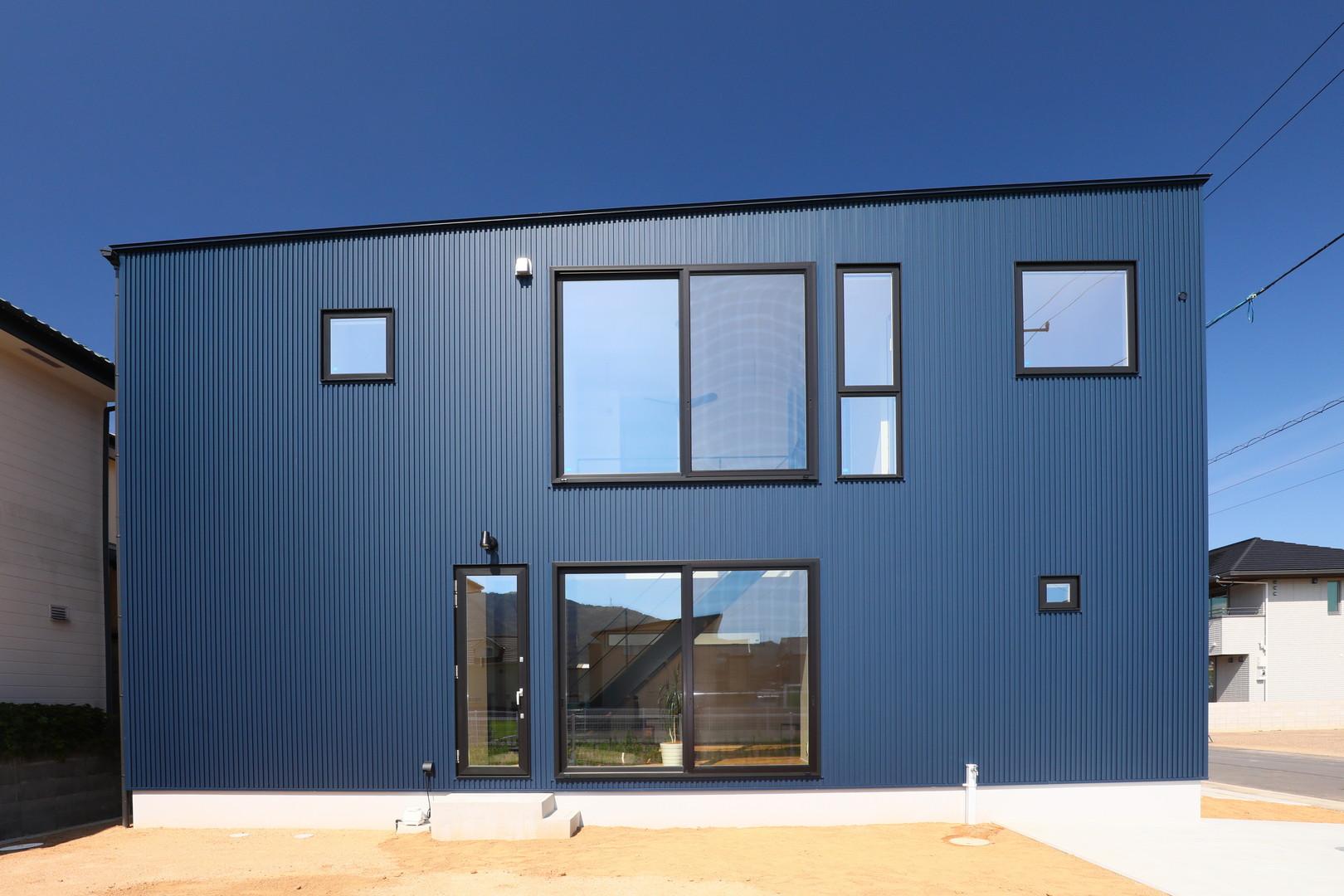 青空へかけ上がる階段と吹き抜けのある家